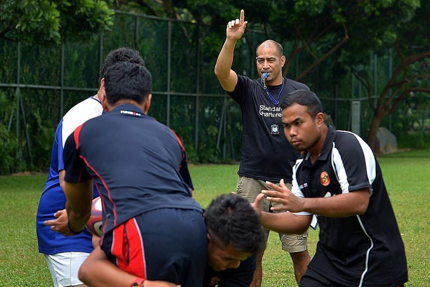 Inoke Afeaki (with hand raised), technical director and head coach of the national rugby team, giving instructions during a training session in 2013.