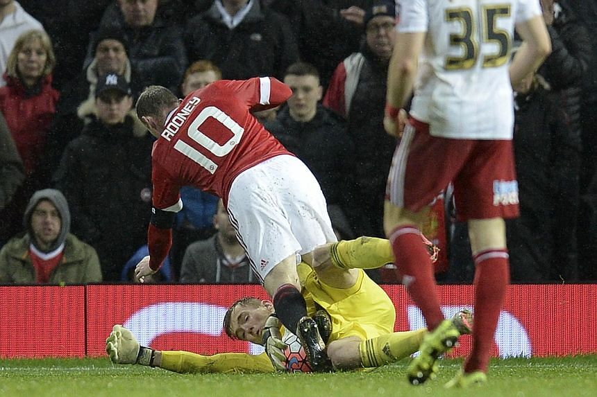 Sheffield United goalkeeper George Long (floor) making a save at the feet of Manchester United striker Wayne Rooney on Saturday. It took a penalty from Rooney to see off United's League One opponents.