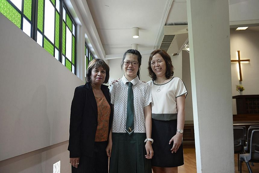 Janessa Yu with her English teacher Shamini Rajandran and Chinese teacher Florence Chang at St Margaret's Secondary School yesterday. Janessa has Charcot-Marie-Tooth disease, which causes a gradual loss of muscle tissue and sense of touch.