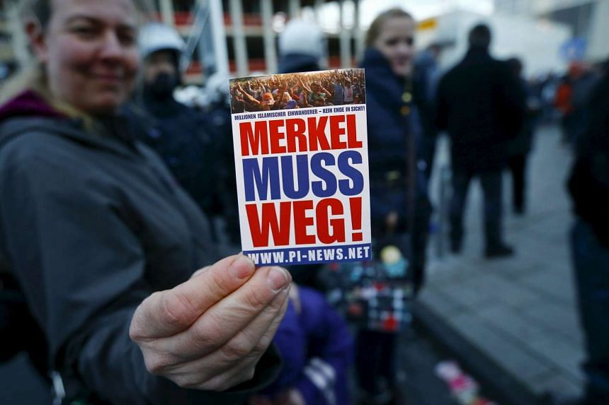 """An anti-immigration supporter during a demonstration rally in Cologne, Germany on Jan 9. The sticker reads: """"Merkel must go!""""."""