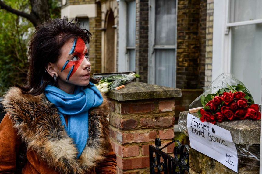 A woman with her face painted, standing outside a house believed to be David Bowie's childhood home, on Jan 11, 2016.
