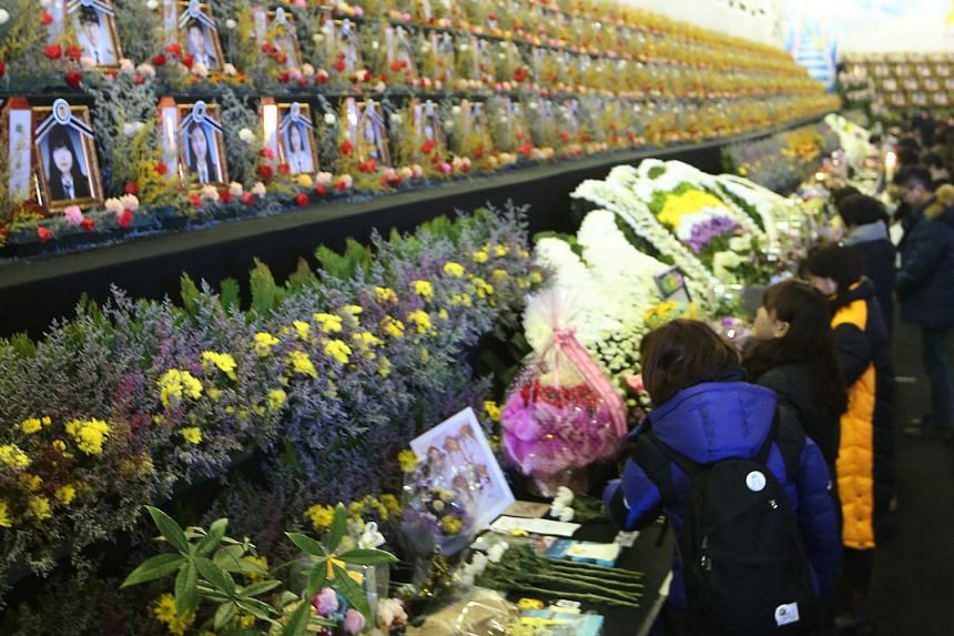 Families of the victims of the Sewol ferry disaster place flowers at an altar in Ansan, South Korea, on Jan 12, 2016.
