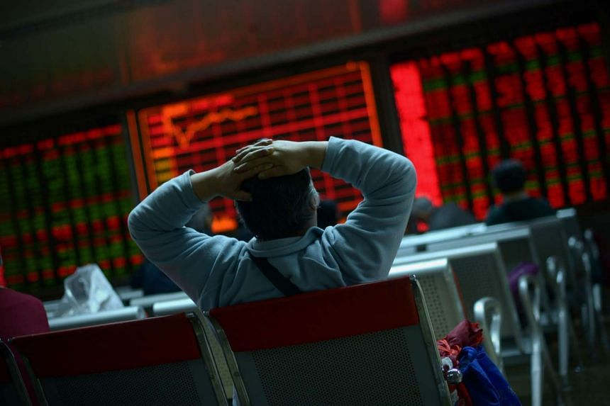 An investor looks at screens showing stock market movements at a securities company in Beijing, on Jan 8, 2016.