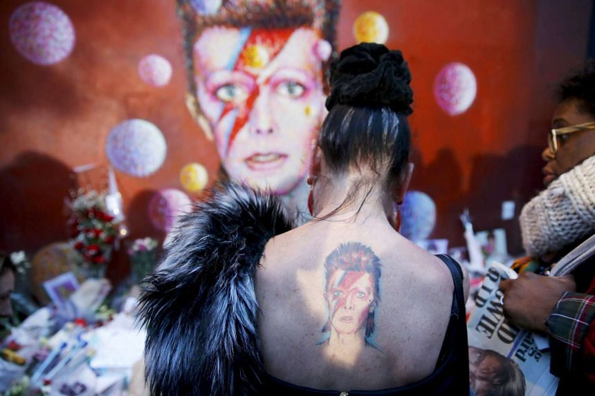 A woman with a Ziggy Stardust tattoo visiting a mural of David Bowie in Brixton, south London, on Jan 11.