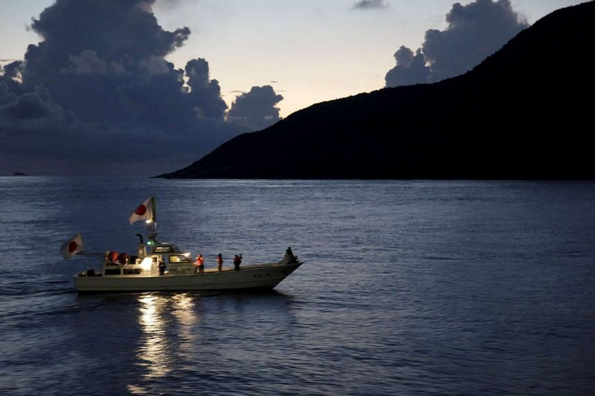 A fishing boat sails around a group of islands known as Senkaku in Japan and Diaoyu in China.
