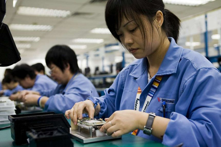 Workers assemble computer devices on the assembly line at the Venture Corp. factory on Dec 15, 2008.