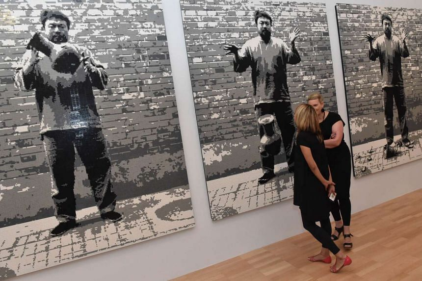 Patrons view Dropping a Han Dynasty Urn , a piece made of Lego blocks by Chinese dissident artist Ai Weiwei.