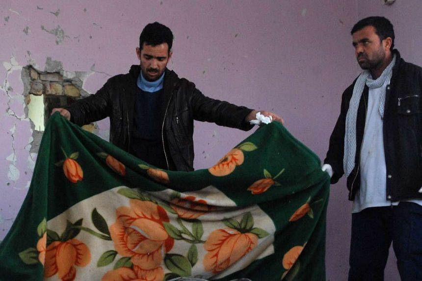 An Afghan security official covers the body of a suspected militant.