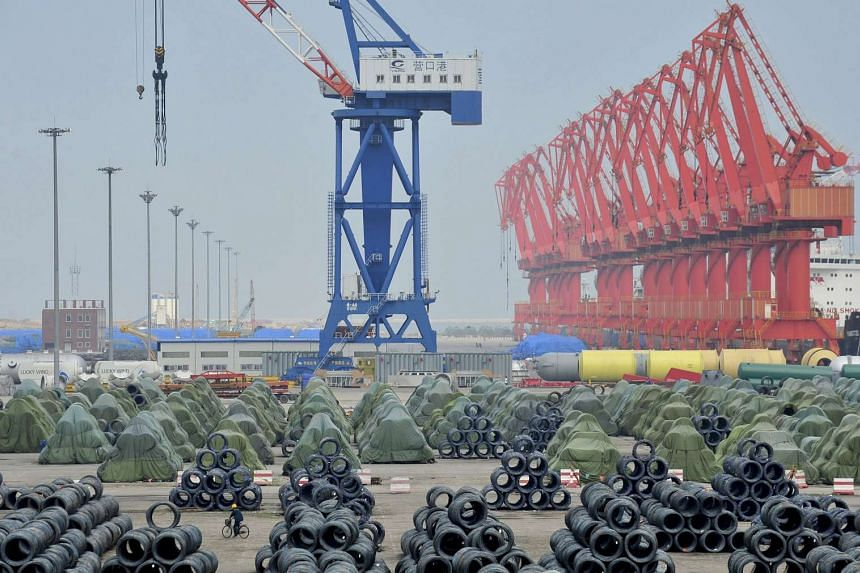 A worker rides his bicycle past piles of steel coils for export at a port in Yingkou, China.