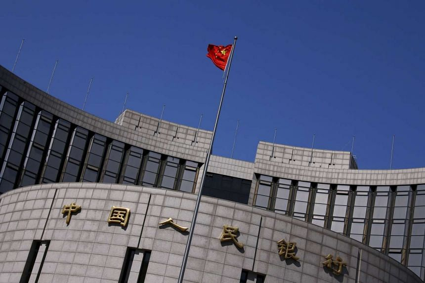 A Chinese national flag flutters outside the headquarters of the People's Bank of China.