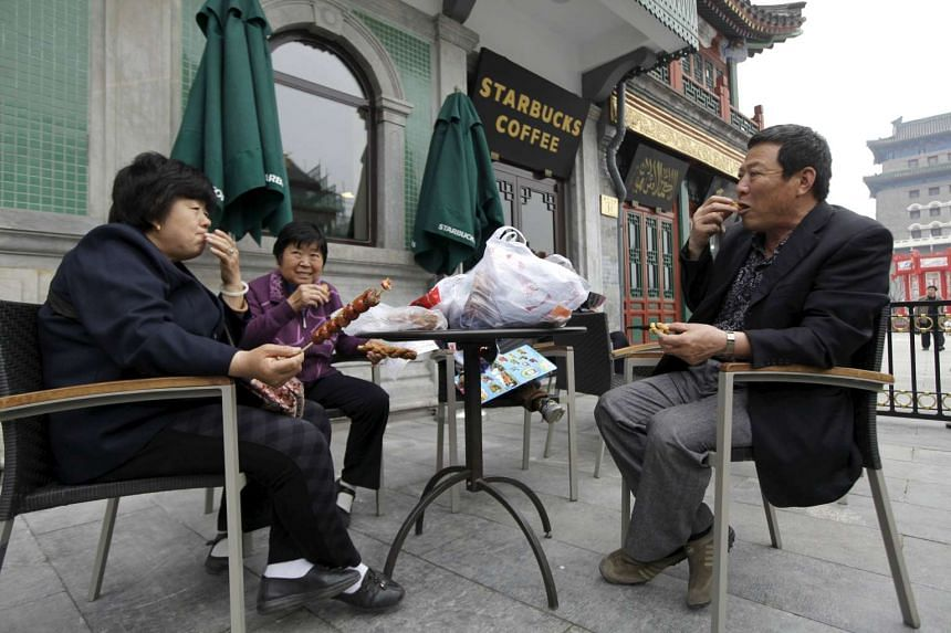 People in a yard of a Starbucks coffee store at Qianmen Commercial Street in central Beijing, China.