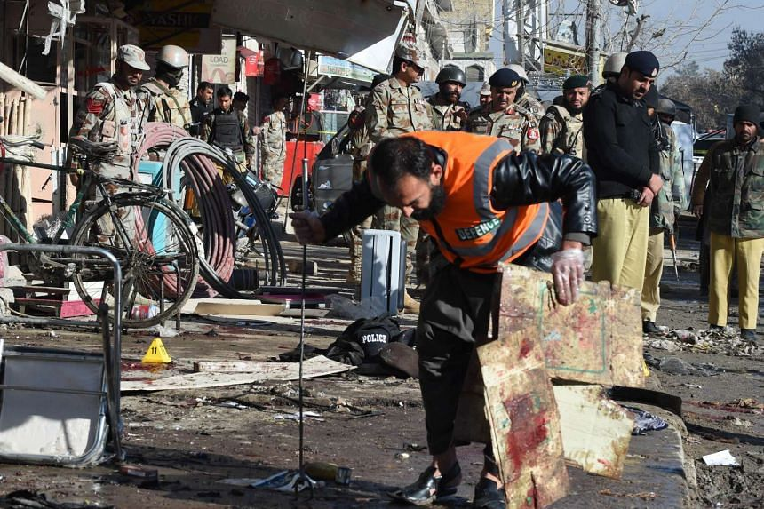Pakistani security officials examine the site of a bomb blast near a vaccination centre in Quetta.