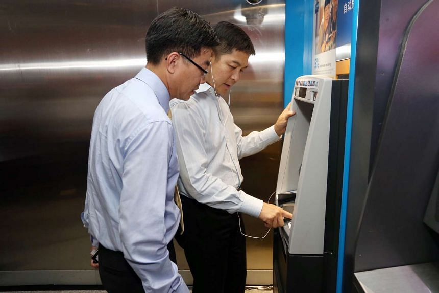 POSB head Derrick Goh and Minister for Social and Family Development Tan Chuan-Jin trying out a Talking ATM.