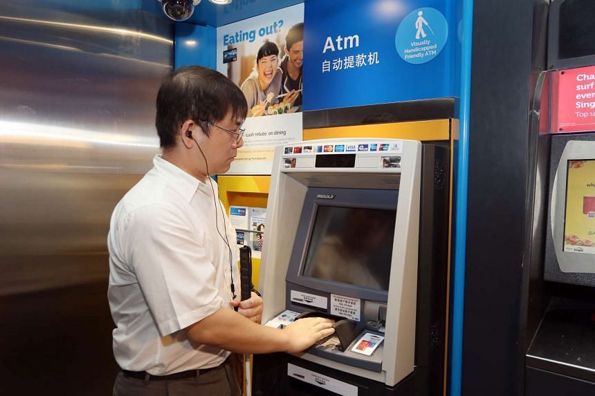 Mr Chong Kwek Bin, 34, who is partially blind, tries out one of POSB's new Talking ATMs at Esplanade Exchange on Jan 12, 2016.