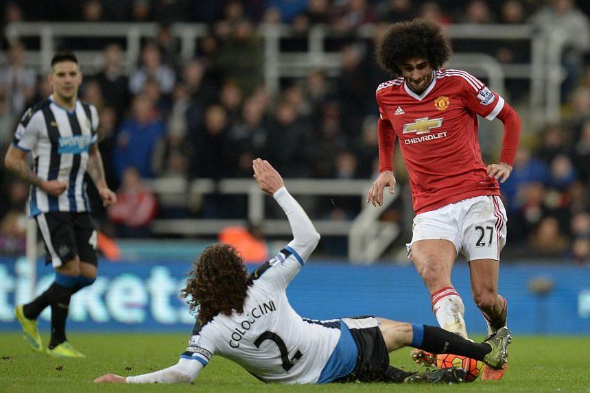 Newcastle United's Fabricio Coloccini (centre) makes a tackle on Manchester United's Marouane Fellaini (right).