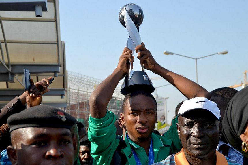 Nigeria's Kelechi Nwakali carries the Fifa Under-17 World Cup trophy on his head at Nnamdi Azikiwe Airport in Abuja, on Nov 11, 2015.