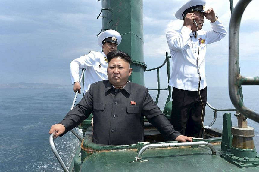 Kim Jong Un (front) stands on the conning tower of a submarine during his inspection of the Korean People's Army (KPA) Naval Unit 167.