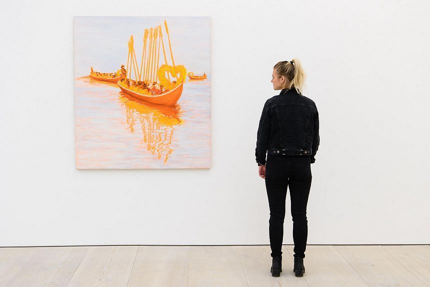 A gallery assistant posing for a photograph with an installation entitled Church Boats by Sigrid Holmwood.