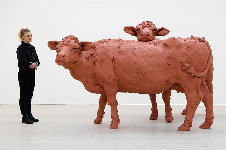 A gallery assistant posing for a photograph with an installation entitled Two Cows by Stephanie Quayle.