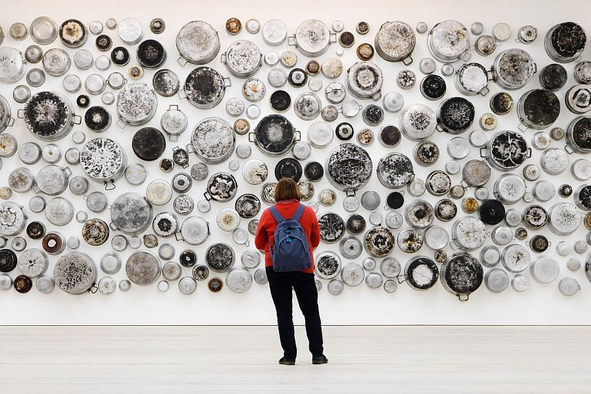 A visitor looking at an installation entitled Untitled (Food For Thought series) by Maha Malluh.