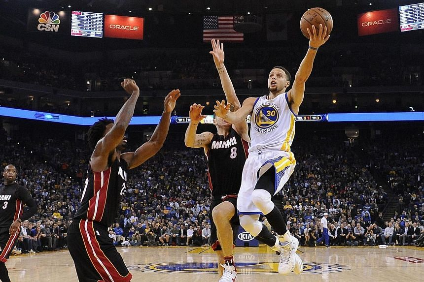 Golden State Warriors guard Stephen Curry (right) shooting against two Miami players. The Warriors cruised to a 111-103 victory over the Heat with Curry recording his 16th 30-point game of the season.