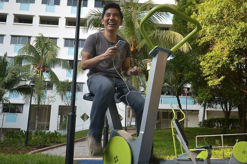 Playpoint managing director Jason Sim demonstrating how to use the outdoor exercise equipment to convert exercise energy into electricity to charge his mobile phone at the Bukit Panjang Ring Road fitness corner.