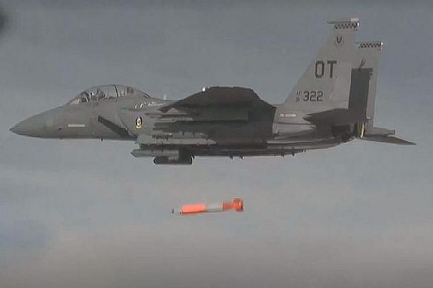 A jet fighter drops a mock B61 Model 12 bomb, which is the United States' first precision-guided atom bomb.