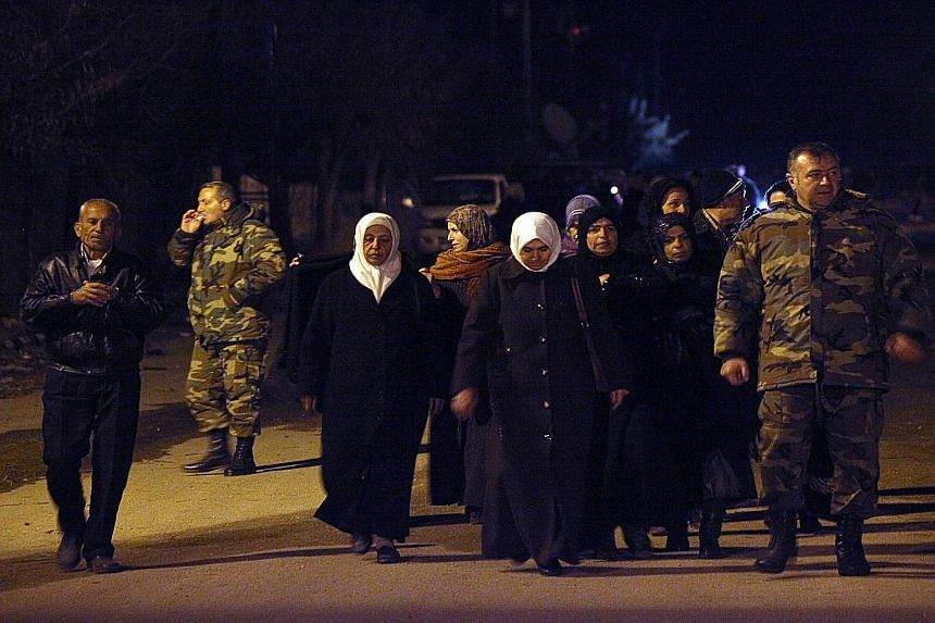 Residents in Madaya walking alongside Syrian soldiers on Monday, the day that the first trucks from a convoy carrying food and medical aid entered the town. Madaya is besieged by pro-government forces, including the Lebanese militia group Hezbollah.