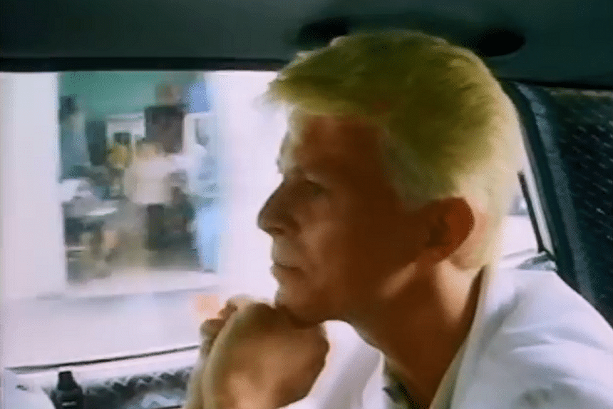 David Bowie chats with a taxi driver in Singapore in the film Ricochet.