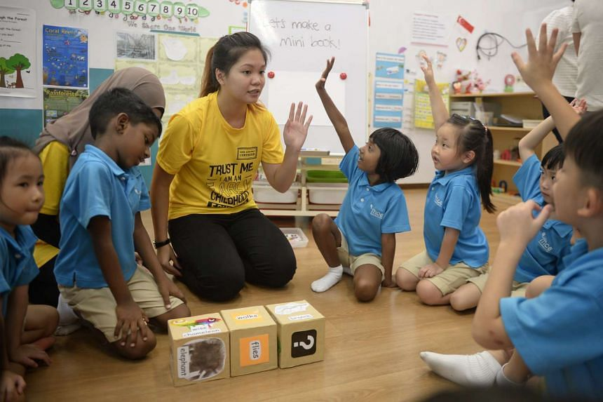 NP Child Psychology and Early Education student Eden Yeong, 19, playing a game of word dice with children at the MOE Kindergarten at Dazhong Primary.