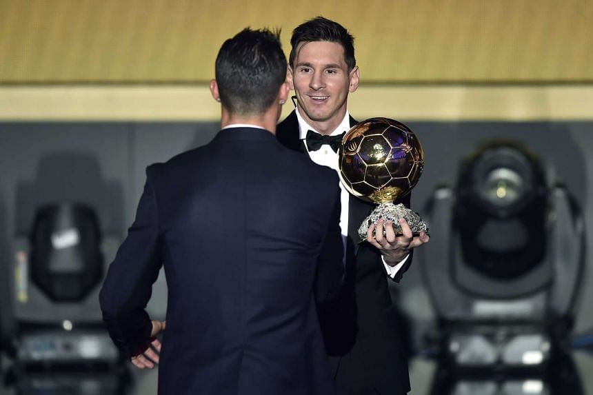 Lionel Messi (right) holds his Fifa Ballon d'Or player of the year trophy as he shakes hands with Cristiano Ronaldo.