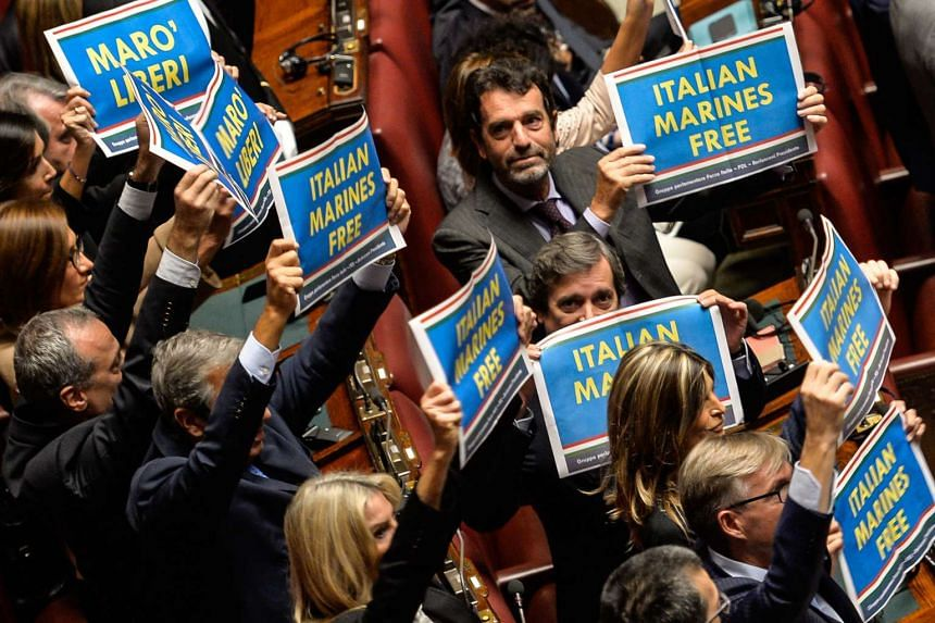 Italy's right-wing lawmakers hold placards asking for the release of Italian marines, detained in India since 2012.