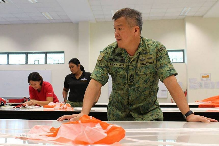 Officer Commanding of the Aerial Delivery Wing, MWO Rickey Yeo, sharing the importance of safety procedures during the stages of the 7-stage parachute packing process.