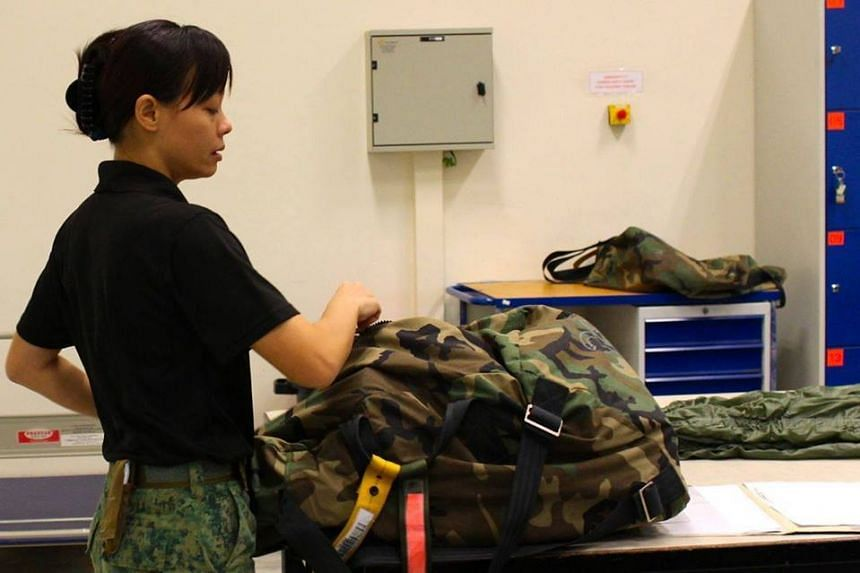 3WO Shirley Ng, an SAF Rigger of the Aerial Delivery Wing packing a parachute.