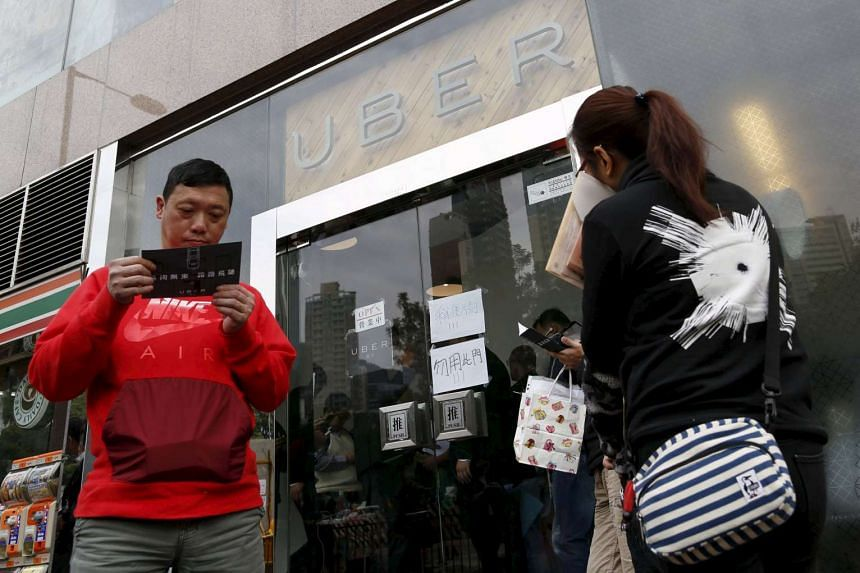 Drivers wait outside the office of taxi-hailing service Uber during a driver recruitment event in Hong Kong, China Dec 29, 2015.