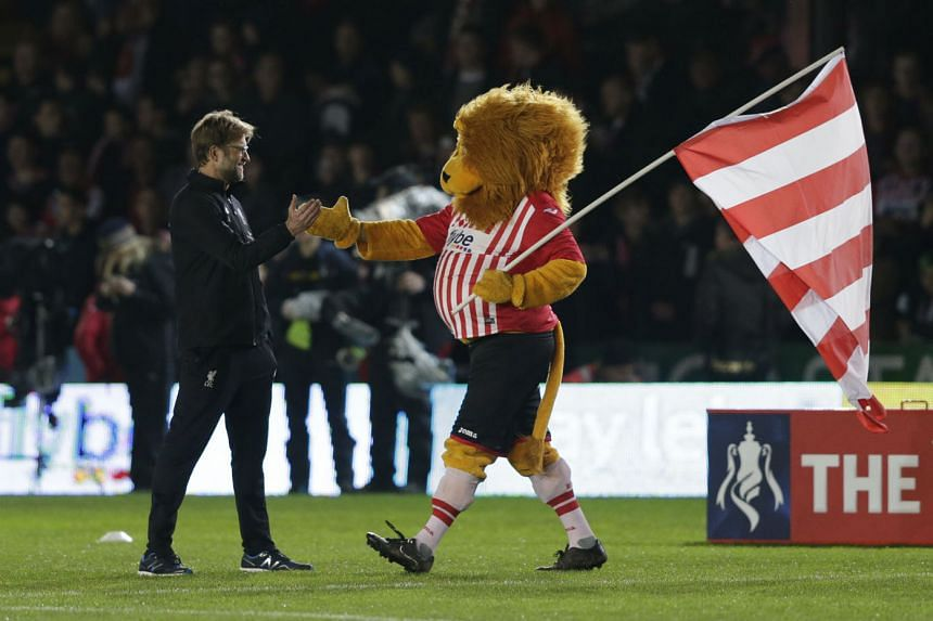 Liverpool manager Juergen Klopp getting friendly with Exeter City's mascot Grecian the Lion before the FA Cup third-round match at St James Park.