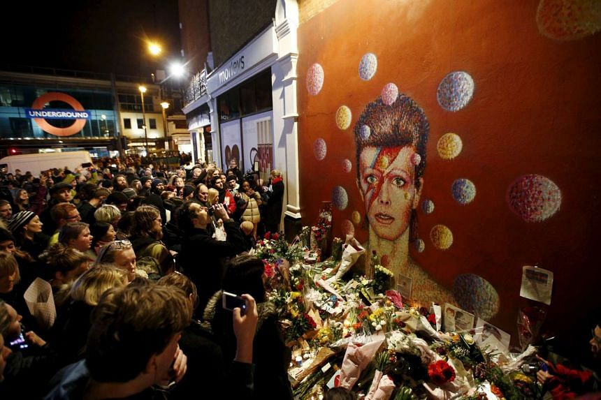 LONDON: Fans stand by floral tributes at a mural of David Bowie (above) in Brixton; and some with painted faces outside Ritzy cinema in south London to pay homage to him following the announcement of his death.