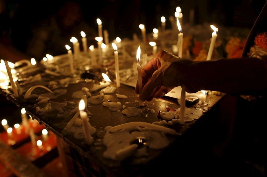 A woman lights a candle during a memorial service for the victims of the attack in Mumbai, India, Jan 6, 2016.