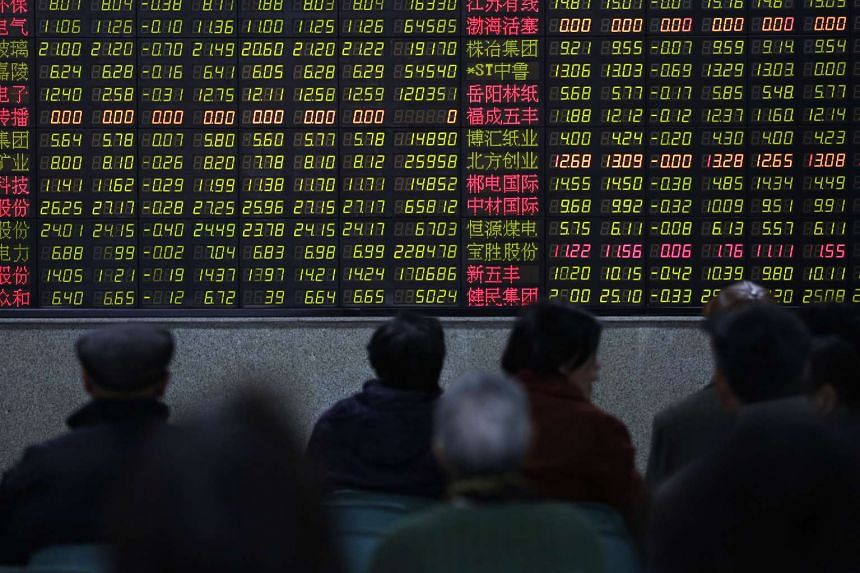 Investors look at an electronic board showing stock information at a brokerage house in Shanghai.