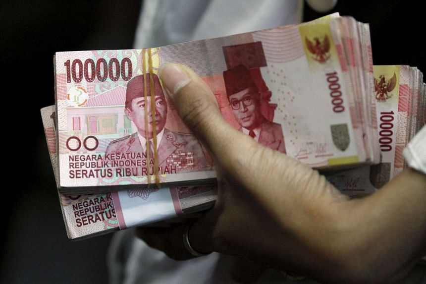 A teller holds Indonesian rupiah bank notes at a money changer in Jakarta.