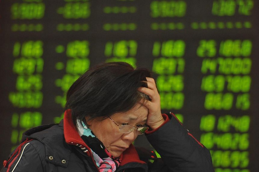 A stock investor checks prices in a brokerage house in Fuyang in central China's Anhui province, on Jan 11, 2016.