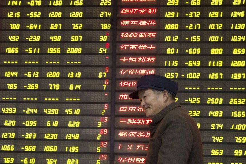 An investor walks past an electronic board showing stock information at a brokerage house in Nanjing, China, on Jan 13, 2016.