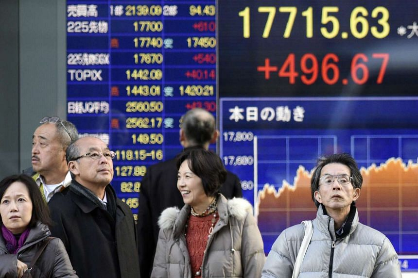 Pedestrians stand in front of a stock market indicator board in Tokyo on Jan 13, 2016.
