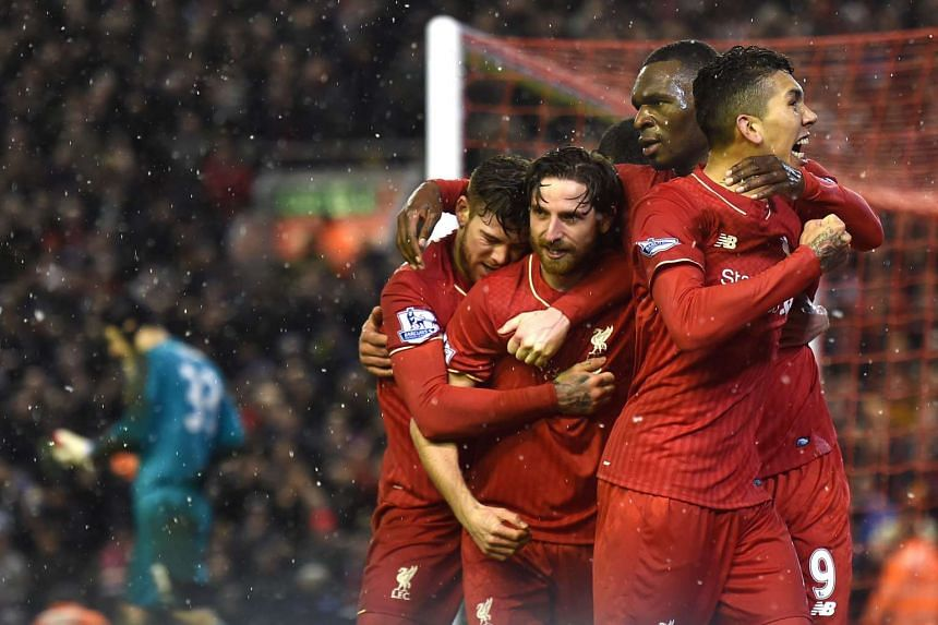 Joe Allen (centre) celebrates with teammates after scoring during the English Premier League football match between Liverpool and Arsenal.