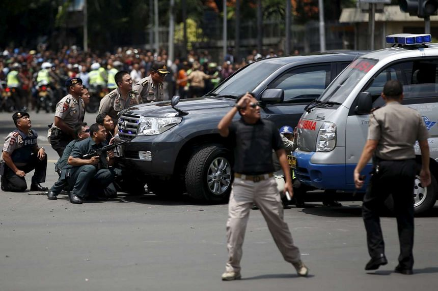 Police officers react near the site of a blast in Jakarta, Indonesia, Jan 14, 2016.