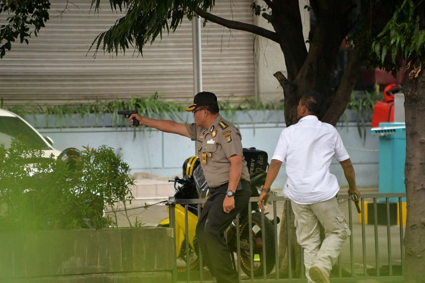 An Indonesian policeman fires his handgun towards suspects outside a cafe after a series of blasts hit the Indonesia capital Jakarta on Jan 14, 2016.
