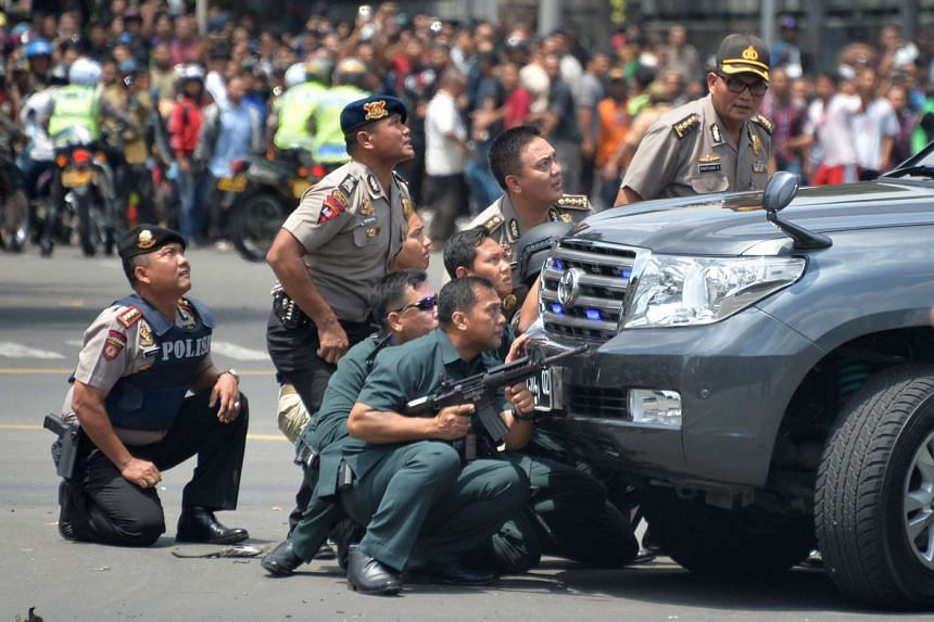 Indonesian police taking position behind a vehicle as they pursue suspects in Jakarta on Jan 14, 2016.