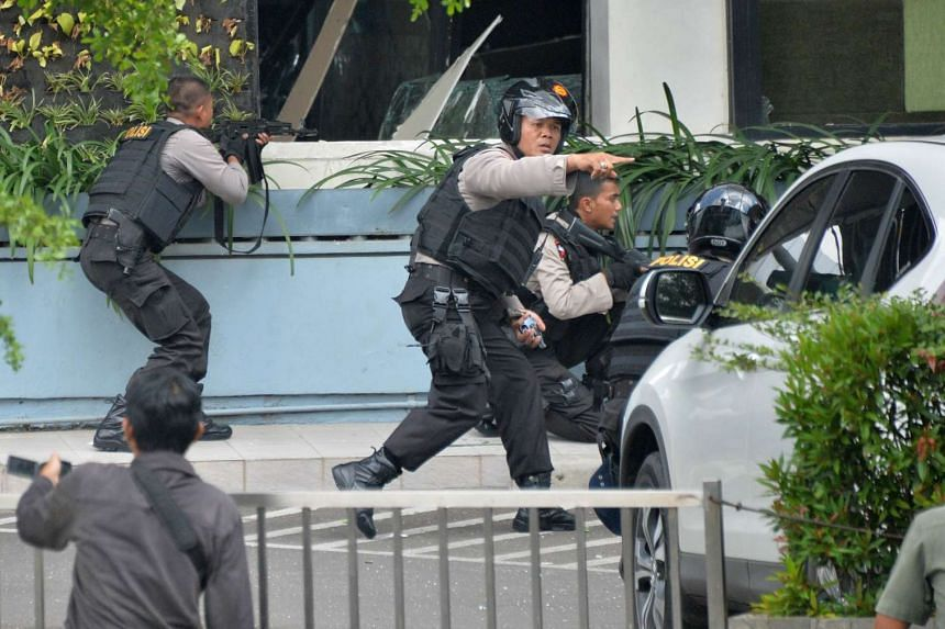 Indonesian police aiming their weapons as they pursue suspects outside a cafe in Jakarta on Jan 14, 2016.