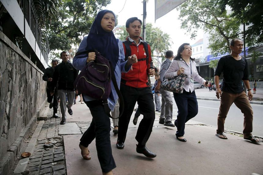 People running as they are evacuated from their office at Thamrin business district in Jakarta on Jan 14, 2016.