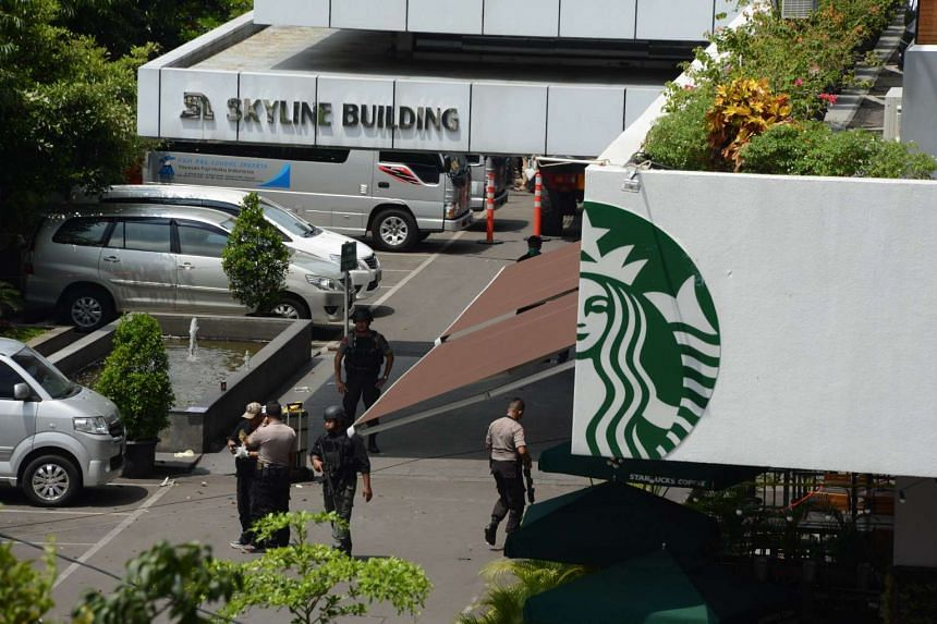 Indonesian police securing the area outside a damaged Starbucks outlet after a blast in Jakarta on Jan 14, 2016.